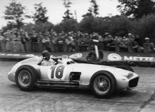 Black and white photo of Juan Manual Fangio driving the Mercedes W1969R